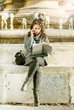 Teenage girl / young student looking at her notebook and talking on the phone Royalty Free Stock Images