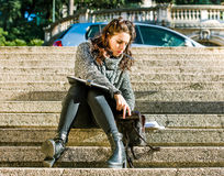 Teenage girl / young student searching in her bag. Teenage girl / young student with dark hair and grey coat sitting on stairs and searching for something in her Royalty Free Stock Photography