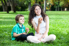 Teenage girld and kid. A teenage asian caucasian girl with long curly brown hair with a boy laughing and having good time sitting on the green grass in the park Royalty Free Stock Photography