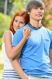Teenage girlfriend hugging her boyfriend in park Royalty Free Stock Photography