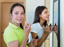 Teenage girlfriends having fun near mirror Royalty Free Stock Photo