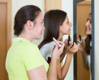Teenage girlfriends having fun near mirror Royalty Free Stock Photography