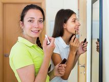 Teenage girlfriends having fun near mirror Royalty Free Stock Images
