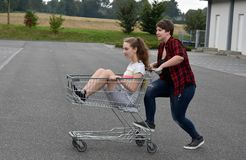 Teenage girlfriends having fun with shopping cart. Teenage girlfriends having fun  with shopping cart at the parking area of a supermarket Royalty Free Stock Images