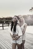 Teenage girlfriends by lake Royalty Free Stock Photography