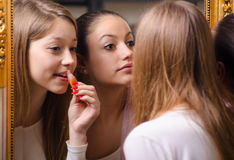 Teenage girlfriends putting make up in front of the old mirror Stock Photo