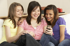 Teenage Girlfriends Reading Mobile Phone at Home Stock Photo