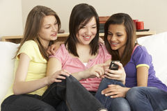 Teenage Girlfriends Reading Mobile Phone at Home Stock Image