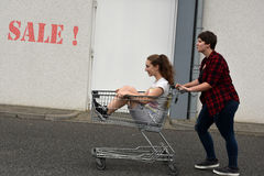 Teenage girlfriends with shopping cart Stock Images