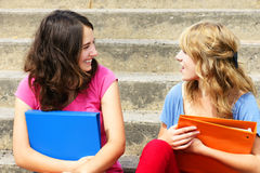 Girlfriends talking. Teenage girlfriends talking and laughing at school royalty free stock photos