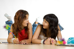 Teenage girls. Two teenage girls laying on the floor writing and talking Stock Image