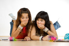 Teenage girls. Two teenage girls laying on the floor writing and talking Royalty Free Stock Images