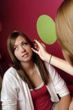 Teenage girls applying makeup Stock Photos