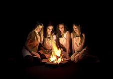 Teenage girls around campfire. Group of four teenage girls wearing aprons sitting around a campfire.  Isolated against a black background Royalty Free Stock Image