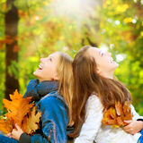 Teenage Girls in Autumn Park. Beautiful Teenage Girls having fun in Autumn Park Royalty Free Stock Image
