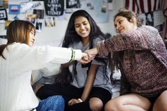 Teenage girls in a bedroom fist bumping friendship concept Stock Images