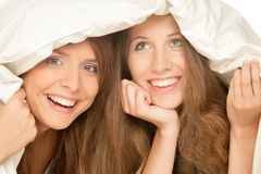 Teenage girls below duvet smiling Royalty Free Stock Photos
