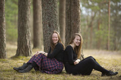 Teenage girls best friends sitting in the forest . Stock Photos