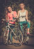 Teenage girls with bicycle in a park on sunny day Stock Photo