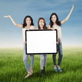 Teenage girls with billboard on meadow Stock Photos