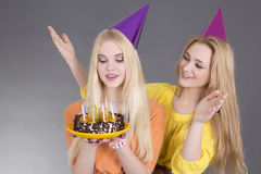 Teenage girls with birthday cake over grey Royalty Free Stock Photo