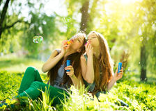 Teenage girls blowing soap bubbles. Joyful teenage girls laughing and blowing soap bubbles Stock Photography
