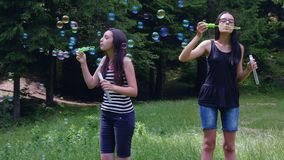 Teenage girls blowing soap bubbles in summer time. Teenage girls blowing soap bubbles and having fun in summer time. Slow motion 4k handheld movement stock footage