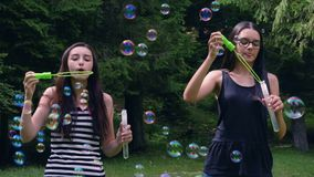 Teenage girls blowing soap bubbles in summer time. Teenage girls blowing soap bubbles and having fun in summer time. Slow motion 4k handheld movement stock video