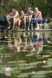 Teenage Girls And Boys With Backpacks Sitting By Lake Royalty Free Stock Photo