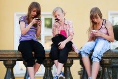 Teen girls calling on mobile phones in city street. Group of teenage girls calling on mobile phones in city street Royalty Free Stock Images