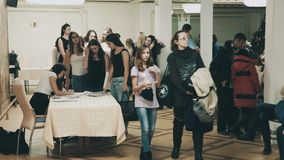 Teenage girls crowd in line to table to get number tag in white hall. Teenage modeling school pretty girls crowd in line to table to get number tag in white hall stock footage