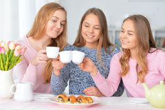 Teenage girls drinking tea. Teenage girls sitting at table and drinking tea with cookies Royalty Free Stock Image