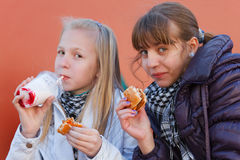 Teenage girls eating a burgers Royalty Free Stock Photos