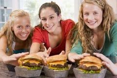 Teenage Girls Eating Burgers. Smiling Stock Image