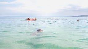 Teenage girls enjoy sea bathing on swimming mattress and in diving masks