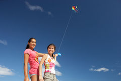Teenage girls flying a kite Royalty Free Stock Images