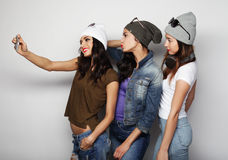 Teenage girls friends in hipster outfit   make selfie on a phone Stock Photos