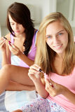 Teenage girls friends painting nails. Smiling Stock Photo