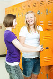 Teenage Girls Gossip by Lockers. Two teenage girls talking by the lockers in the hallway of their high school royalty free stock images