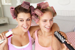 Teenage girls with hair in curlers. Having fun Royalty Free Stock Images