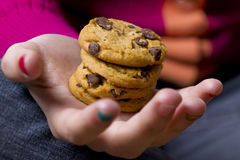 Teenage girls hand and cookies Royalty Free Stock Photos