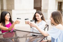 Teenage girls having coffee at cafe. Happy teenage girls having fun and making a toast with coffee at outdoor cafe Royalty Free Stock Photography