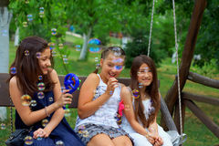 Teenage girls having fun blowing bubbles in park Stock Image