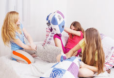 Teenage girls  having fun. And fighting with pillows Stock Image