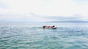 Teenage girls having fun with inflatable mattress in blue sea