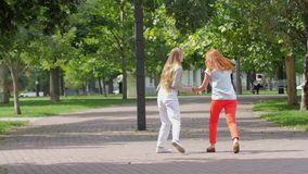 Teenage girls having fun and jumping in spring. Beautiful teenage girls having fun in spring park. Outdoor. slow motion stock video footage