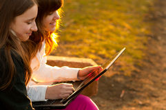 Teenage girls having fun with notebook. Two beautiful teenage girls having fun with notebook in the park on sunny spring day Royalty Free Stock Photos
