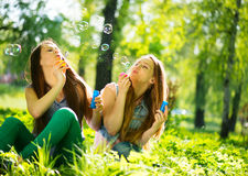 Teenage girls having fun outdoors. Joyful teenage girls laughing and blowing soap bubbles Royalty Free Stock Photography