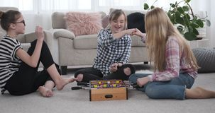 Teenage girls having fun while playing foosball. Teenage girl friends having fun while playing foosball at home stock video footage