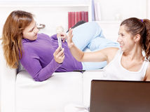 Teenage girls having fun using electronic gadgets Royalty Free Stock Image